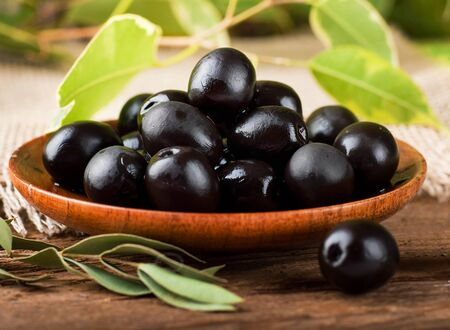 Black olives in a wooden plate and a rough board Stock Photo - 17092333