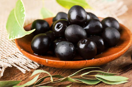 Black olives in a wooden plate and a rough board Stock Photo - 17092343