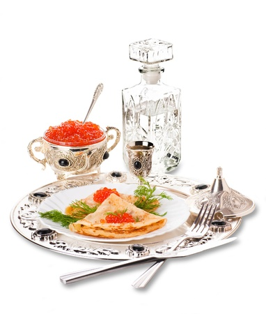 Pancakes with red caviar on silver ware photo