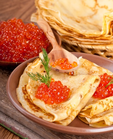Pancakes with red caviar on wooden ware photo