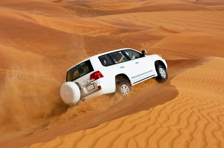 DUBAI - JUNE 2: Driving on jeeps on the desert, traditional entertainment for tourists on June 2, 2013 in Dubai