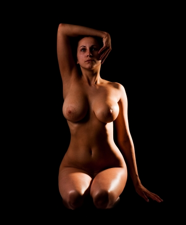 The naked young girl on a black background