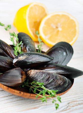 Mussels in the shell with lemon on wooden background photo