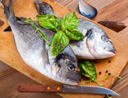fish store: Dorado fish with lemon and spices on a wooden board Stock Photo