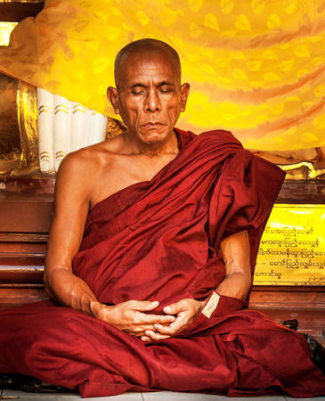 Yangon - November 30: Shwedagon Pagoda November 30, 2013 in Yangon. Monks pray at the foot of deities
