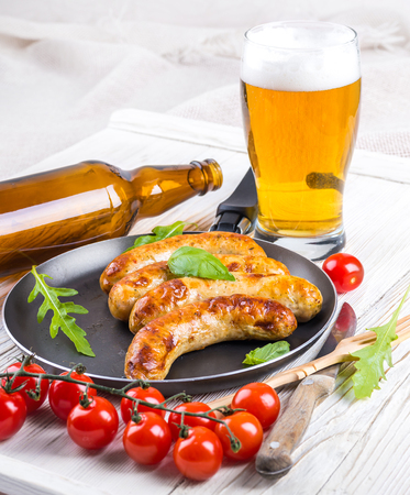 The Munich sausages with tomatoes and arugula Stock Photo - 25400170