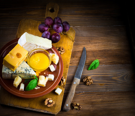 Different varieties of cheese with walnuts and grapes photo