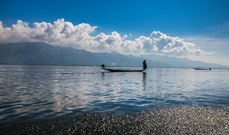 Fishermen and their reflection in the water on the Inle Lake, Myanmar photo