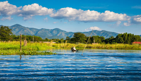 Ancient houses and their reflection in the water on the Inle Lake, Myanmar photo