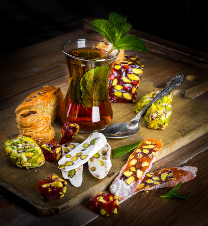 Tea in a glass with Turkish sweets photo