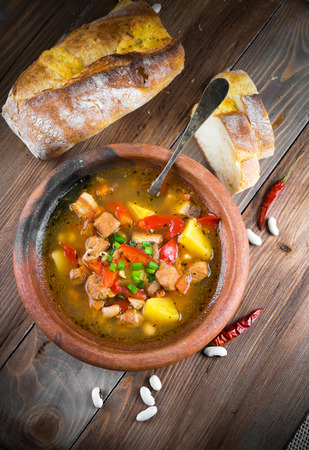 Hungarian goulash with beans and peppers on wooden board photo