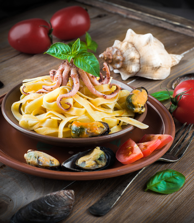Pasta with mussels and octopus on wooden background photo