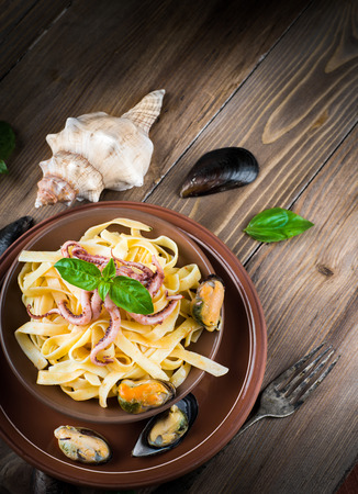 marinara: Pasta with mussels and octopus on wooden background