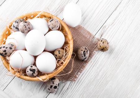 Kwartels en kippen eieren in een rieten mand op een houten plank Stockfoto