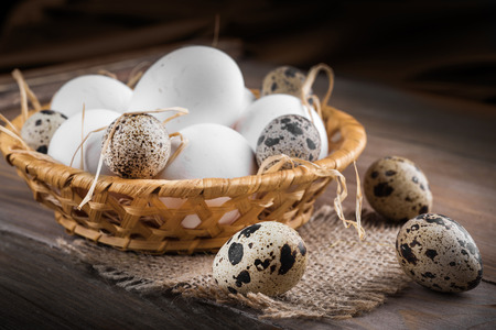 Quail and chicken eggs in a wicker basket on a wooden board photo