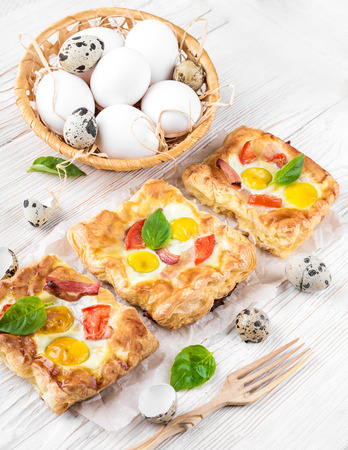 Pie of quail eggs with tomato and bacon photo