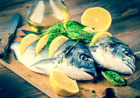 Dorado fish with lemon and spices on a wooden board photo