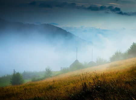 Amazing mountain landscape with fog and a haystack photo