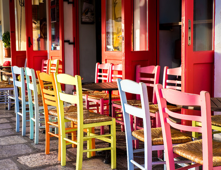greek island: Greek island restaurants with colorful tables and chairs. Stock Photo