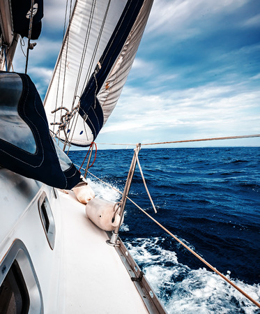 yacht: The white sails of yachts on the background of sea and sky in the clouds Stock Photo