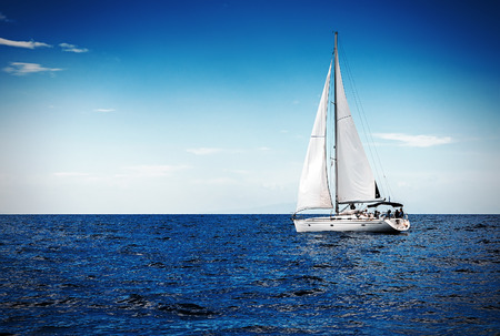 The white sails of yachts on the background of sea and sky in the clouds Banque d'images