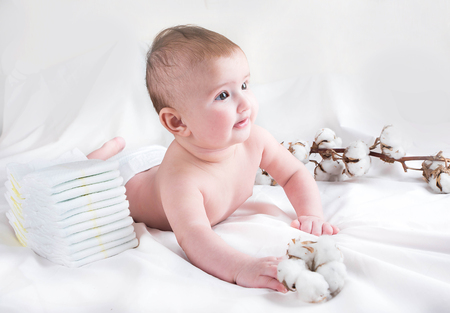 Baby in diaper on a white background with a branch of cotton