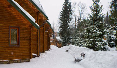 Christmas winter landscape, old wooden house, surrounded by snow-capped fir trees