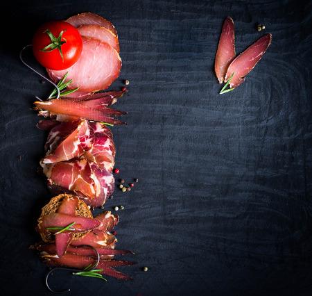 Un conjunto de diferentes tipos de carne ahumada cruda. Jamón Lomo, Ñ oppa y filete sobre fondo negro.