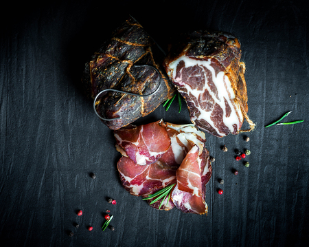 A set of different types of raw smoked meat. Jamon Lomo, сoppa and fillet on a black background. Zdjęcie Seryjne