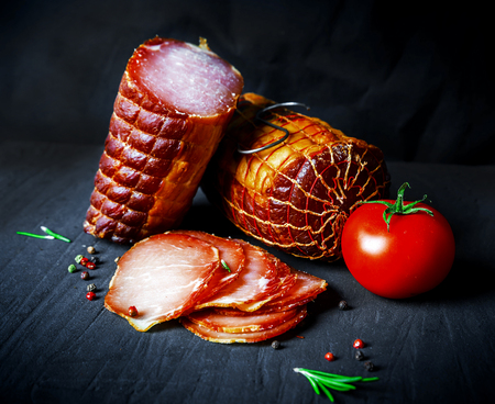 A set of different types of raw smoked meat. Jamon Lomo, сoppa and fillet on a black background. Stock Photo