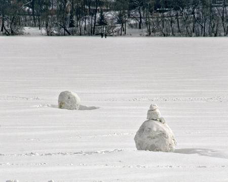 Partially built snowmen on Lake Harriet in Minneapolis, Minnesota.