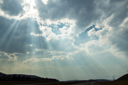 God-rays shine through the clouds outside of Kananaskis country.