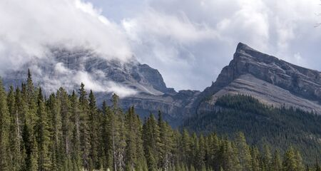 Two mountain peaks in Kananaskis country. One veiled by clouds, the other not.