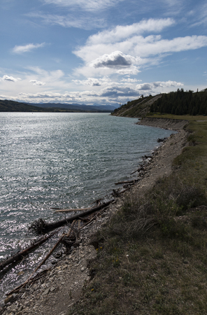 The shore of Ghost Lake (Alberta, Canada) with the Canadian Rockies visible in the distance.