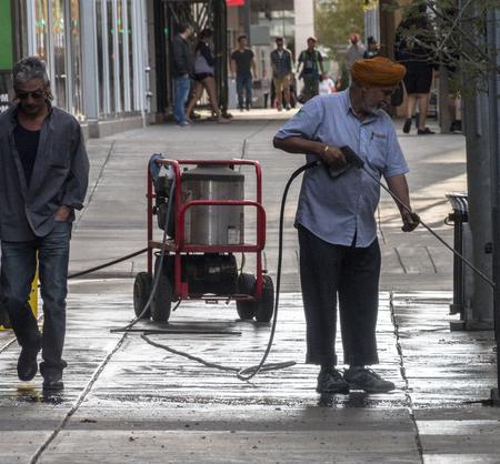 Calgary, AlbertaCanada – August 30, 2015: A man pressure-washing a sidewalk outside of a business in Calgary, Alberta.