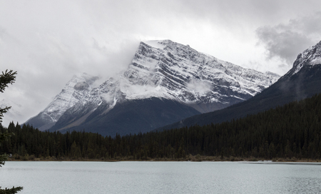 Beautiful mountains surrounded by clouds along the Bow River in Alberta, Canada.