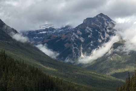 Low-flying clouds hug the contours of a mountain in Banff National Park, Alberta, Canada.