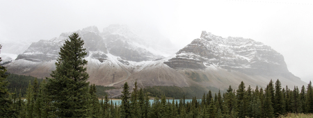 A shot of the beautiful Canadian Rockies along the Bow River, obscured by the haze of clouds.