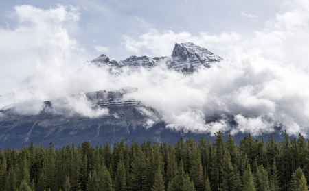 Clouds hang low and surround a mountain in the Canadian Rockies in Alberta, Canada.