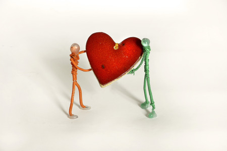 dollhouse: two wire people carrying red wooden heart