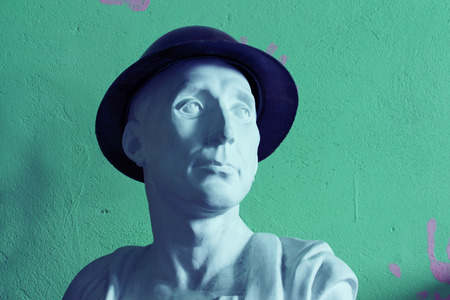 bust: plaster bust in hat on green background