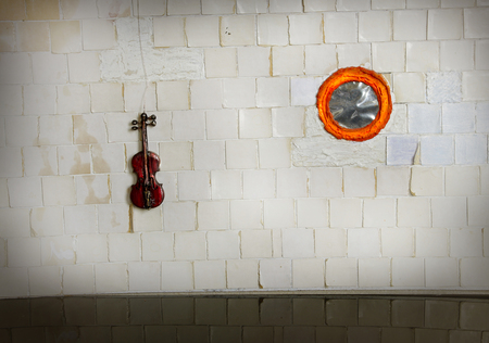 dollhouse: violin on white tile wall