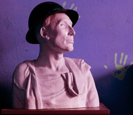 bust: plaster bust in hat on violet background