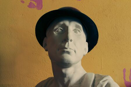 bust: plaster bust in hat on orange background