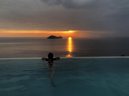 美しい夕日の背景にプールで女の子
