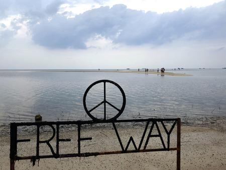遠くにビーチと砂の島、木製の棒の海岸に碑文