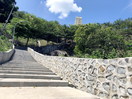 the stairs are of concrete, with stone walls leading up the mountain in an Indian temple