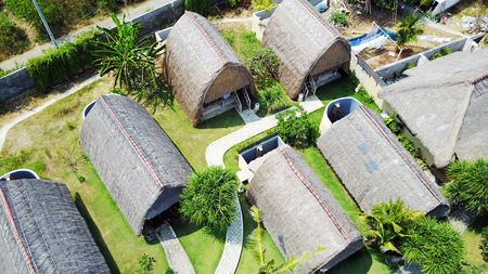 wooden bungalows with thatched roofs on the island of Penida in Indonesia