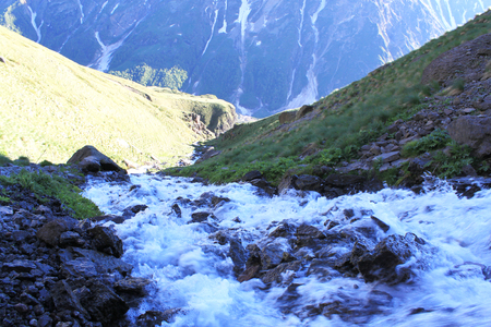 the river from the waterfall girlish braids or Carabasi-su, in Kabardino-Balkaria, near mount Elbrus, a mountain river flowing down the rocks rushing water and mountains in background with green grass
