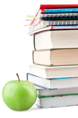 Textbooks and notebooks next to the green apple on white background photo